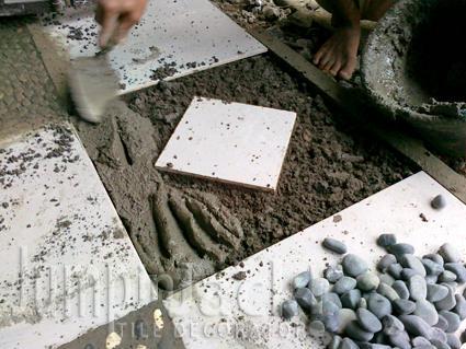 Beri adukan semen pada bagian yang akan dipasang batu koral.