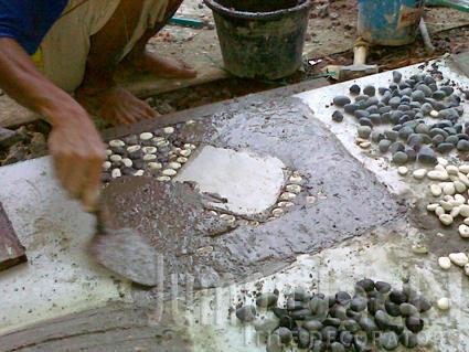 Ratakan agar rongga antar batu koral terisi dengan semen.