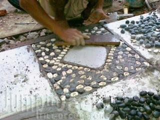 Ketuk sampai permukaan batu sejajar dengan semen dan keramik.